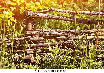 Wicker Rustic Fence In The Summer Garden On Grass Background