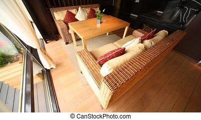 Wicker sofa stand in restaurant lounge fenced  from of terrace by glass door with hangings