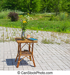 Wicker table with wild flowers bouquet in a vase