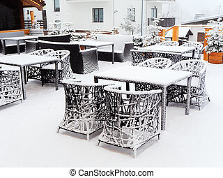 Wicker tables and chairs strewn with snow stand on the terrace of an outdoor cafe on a cloudy snowy day