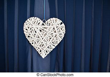 Wicker white heart on a blue background