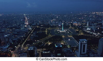 Wide aerial dolly view of Indonesian national monument Monas symbolizing independence in large pubic park in Jakarta