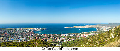 Wide aerial panorama of Gelendzhik resort city, Krasnodar region, Russia. View from hill of Caucasian mountains. Beautiful sea bay in frame.