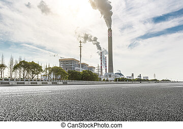 Wide angle landscape photograph of a road leading to a power plant