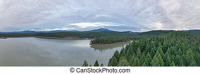 Wide-angle of a lake in the forest with a mountain as background