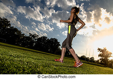 Wide angle picture of running women with sun in background