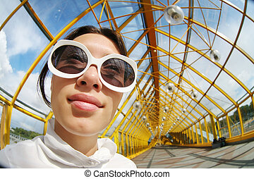 Wide angle portrait of a young woman in sunglasses