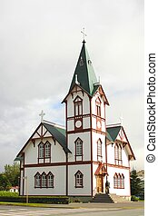 Wide angle shot of the Husavik church at Husavik harbor, Iceland