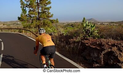 Wide angle tracking shot of a fit male athlete riding bicycle on long flat road in countryside. Man cycling on flat highway road.
