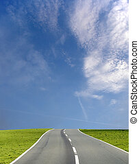 Wide image of a road under a blue sky with soft clouds.