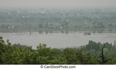 Wide, calm river in front of a faroff city