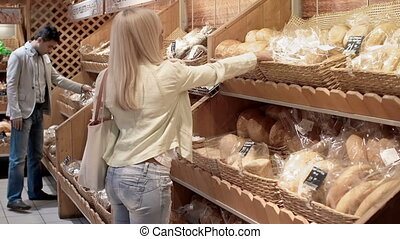 Wide Choice - Blond lady picking bread from shelf, smelling...