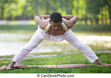 young man working out standing in asana wide legged