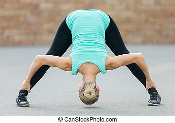woman working out doing wide legged forward bend