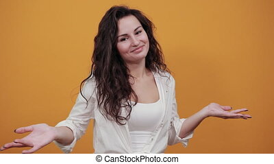 Wide open arms, incredulity, doubt beautiful woman. Is surprised spread palms, mimic and facial expressions. Young attractive woman, dressed white blouse, with brown eyes, curly hair, yellow