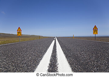 Wide Open Road With Warning Signs - A ground level shot of a...