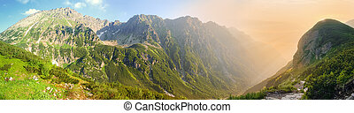 Wide panorama of deep mountain gorge in morning sunlight