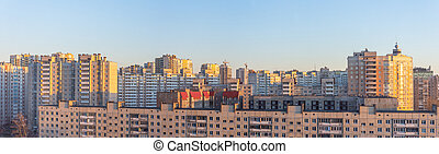Wide panorama view of residential high-rise buildings, in the evening at sunset.