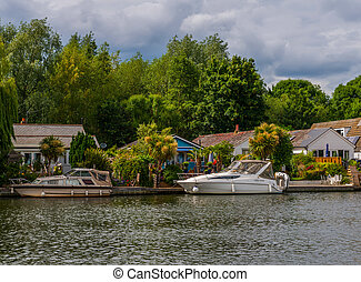 Wide river and houses on the shore, moored boats, green vegetation, a place of relaxation in the city