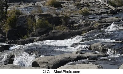 Wide river flowing over the terraced rock mass