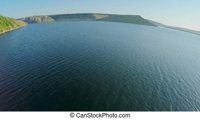 wide river with hilly islands from a bird's-eye view. Dniester, Ukraine, green hills and wanding river