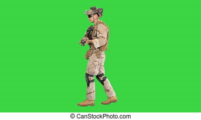 Armed man in camouflage with a gun walking on a Green Screen, Chroma Key.