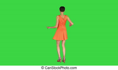 Wide shot. Back view. Girl Dancing in Orange SunDress on a Green Screen, Chroma Key. Professional shot in 4K resolution. 023. You can use it e.g. in your commercial video, business, presentation, broadcast