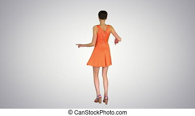 Wide shot. Back view. Girl Dancing in Orange SunDress on gradient background. Professional shot in 4K resolution. 023. You can use it e.g. in your commercial video, business, presentation, broadcast
