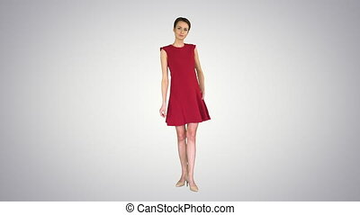 Wide shot. Beautiful young woman with short hair in red dress posing on gradient background. Professional shot in 4K resolution. 023. You can use it e.g. in your commercial video, business, presentation, broadcast
