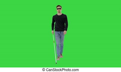 Wide shot. Blind young man with stick walking on a Green Screen, Chroma Key. Professional shot in 4K resolution. 53. You can use it e.g. in your medical, commercial video, business, presentation, broadcast