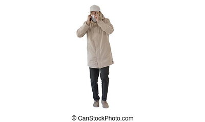 Casual man in outdoor clothes and medical mask walking and talking on the phone on white background.
