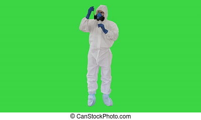 Wide shot. Doctor in Hazmat Suit and Gas Mask Holding Test Tube of Blood on a Green Screen, Chroma Key. Professional shot in 4K resolution. 53. You can use it e.g. in your medical, commercial video, business, presentation, broadcast
