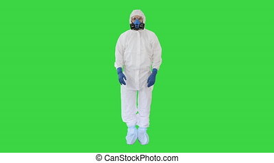 Doctor wearing protective hazard suit showing ok sign and thumb up to camera on a Green Screen, Chroma Key.
