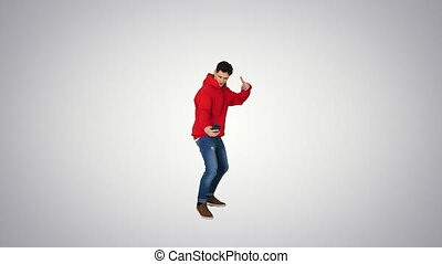 Wide shot. Excited casual man dancing and making selfie with his phone on gradient background. Professional shot in 4K resolution. 022. You can use it e.g. in your commercial video, business, presentation, broadcast