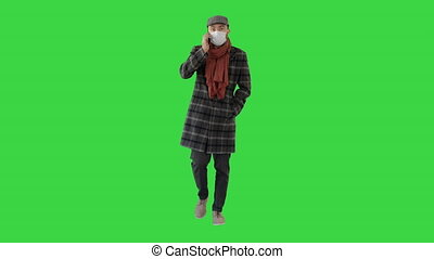 Wide shot. Fashionable gentleman in medical mask calling on the phone on a Green Screen, Chroma Key. Professional shot in 4K resolution. 53. You can use it e.g. in your medical, commercial video, business, presentation, broadcast