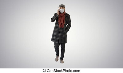Fashionable gentleman in medical mask calling on the phone on gradient background.