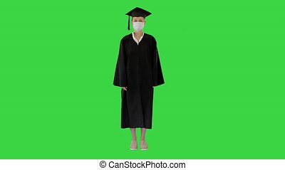 Female graduate student in a medical mask standing on a Green Screen, Chroma Key.