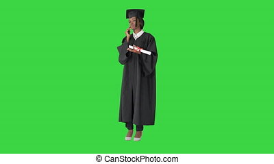 Wide shot. Front view. African American female student in graduation robe talking on the phone on a Green Screen, Chroma Key. Professional shot in 4K resolution. 046. You can use it e.g. in your medical, commercial video, business, presentation, broadcast