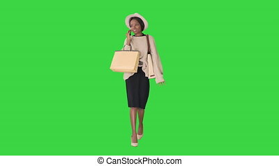 African american girl in oversized knitwear and hat talking ...