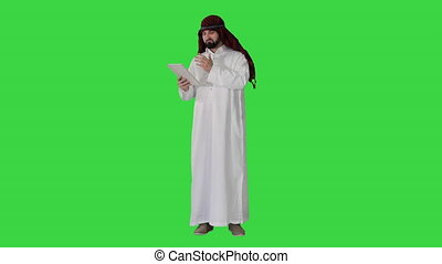 Wide shot. Front view. Arabic business man with tablet on a Green Screen, Chroma Key. Professional shot in 4K resolution. 044. You can use it e.g. in your medical, commercial video, business, presentation, broadcast