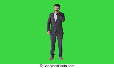 Wide shot. Front view. Businessman using speak activate virtual digital voice assistant on smartphone on a Green Screen, Chroma Key. Professional shot in 4K resolution. 044. You can use it e.g. in your medical, commercial video, business, presentation, broadcast