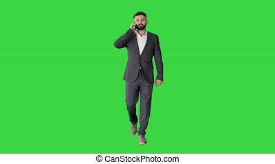 Businessman walking and making a call on a Green Screen, Chroma Key.