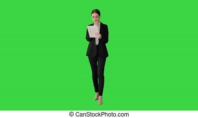 Wide shot. Front view. Businesswoman using a tablet pad while walking on a Green Screen, Chroma Key. Professional shot in 4K resolution. 043. You can use it e.g. in your medical, commercial video, business, presentation, broadcast