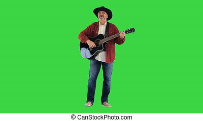 Cowboy man with acoustic guitar singing a song on a Green ...