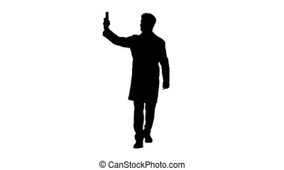 Doctor taking a selfie with smartphone while walking, Alpha Channel