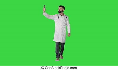 Doctor taking a selfie with smartphone while walking on a Green Screen, Chroma Key.