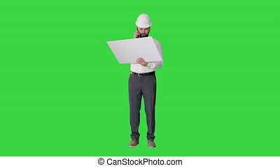 Wide shot. Front view. Engineer in formalwear and hardhat talking to client or contractor on mobile phone and looking at blueprint on a Green Screen, Chroma Key. Professional shot in 4K resolution. 044. You can use it e.g. in your medical, commercial video, business, presentation, broadcast