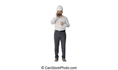 Engineer in white hard hat talking on his mobile phone on ...