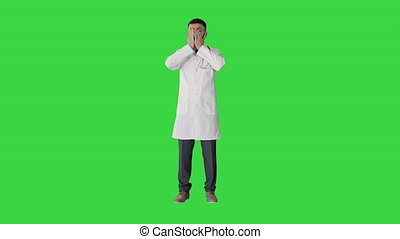 ?epressed doctor holding his head on a Green Screen, Chroma Key.