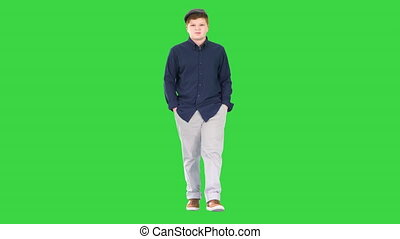 Fashionable young man walking with hands in pockets on a Green Screen, Chroma Key.